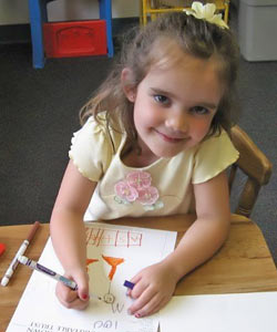 young girl drawing at desk